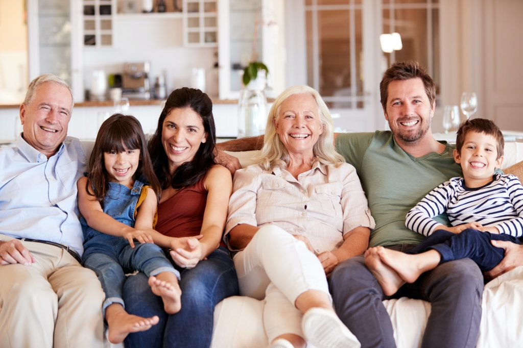 Happy three generation white family sitting on a sofa together at home smiling to camera, front view